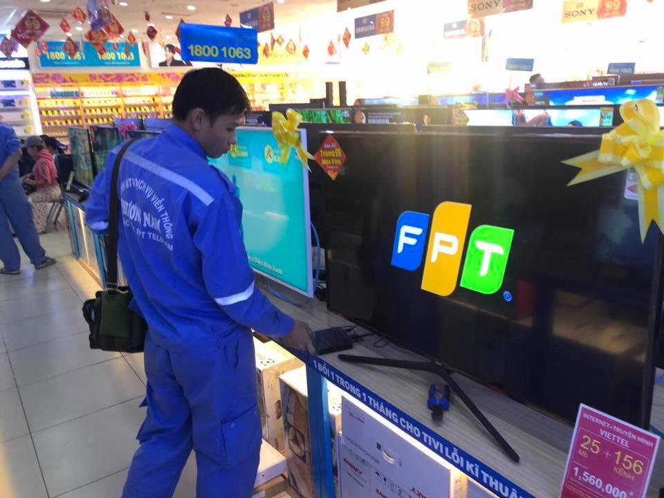 Nhân viên Điện Máy Xanh đang cài đặt truyền hình FPT