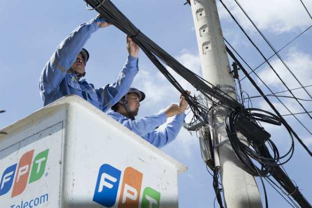 Nhân viên kỹ thuật FPT Telecom HCM lắp mạng Internet cho khách hàng